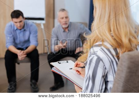 Psychological therapy. Pleasant nice experienced psychologist listening to her patients and taking notes while having a group therapy session