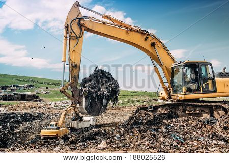 Industrial Excavators And Heavy Duty Machinery Working On Garbage Dump Site.