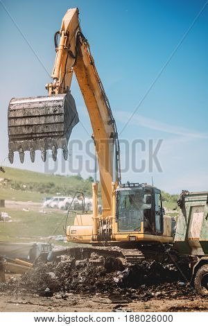 Details Of Heavy Duty Machinery Working On Site. Excavator Loading Dumper Trucks
