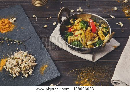 Vegetarian food. Indian restaurant dish with fried tofu cheese, broccoli, mung bean and spices, top view, flat lay