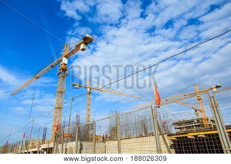 Building crane orange in the background of the sky and the object under construction