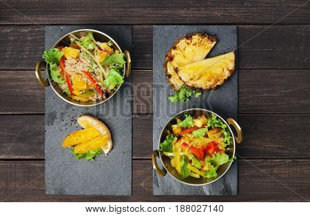 Vegetarian indian food. Healthy vegan salad with pineapple and vegetables in copper bowl on wooden table, top view
