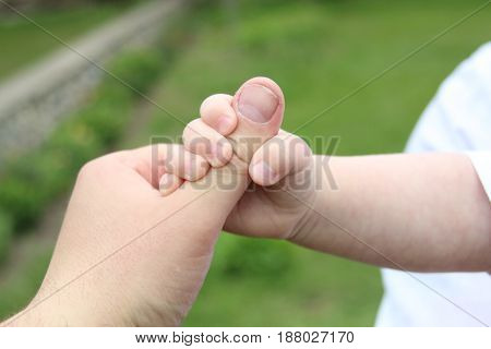 Child's hands, family idea. Newborn baby boy and fathers hand
