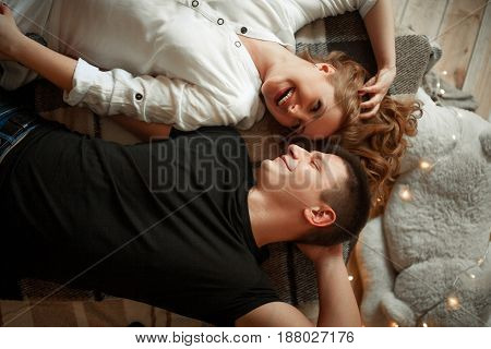 Young enamored woman and man lie side by side on bed and laugh joyfully. They look at each other.