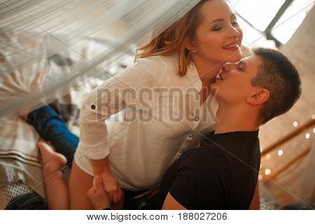 Pregnant woman with her husband sit on bed and hug. He kisses her neck.