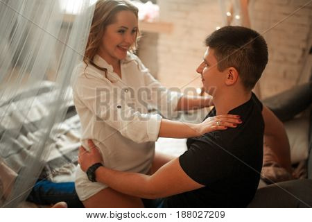 Pregnant woman with her husband sit on bed and hug. She laughs.