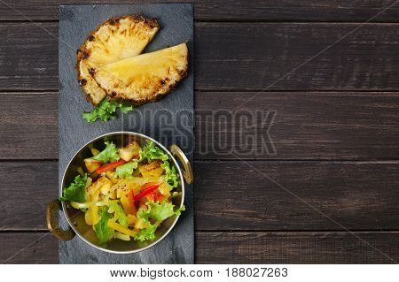 Vegetarian indian food. Healthy vegan salad with orange and vegetables in copper bowl on wooden table, top view