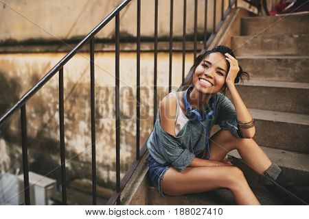 Full length portrait of attractive young woman with charming smile posing for photography while sitting on shabby stairs of apartment house