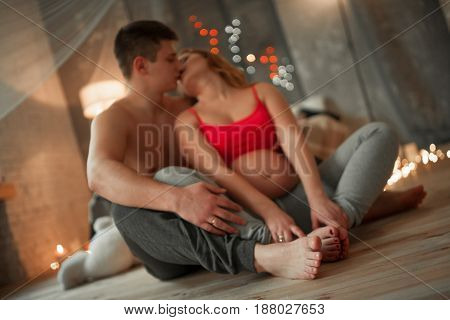 Pregnant woman with her husband sit on wooden floor and kiss. Behind you can see lights.