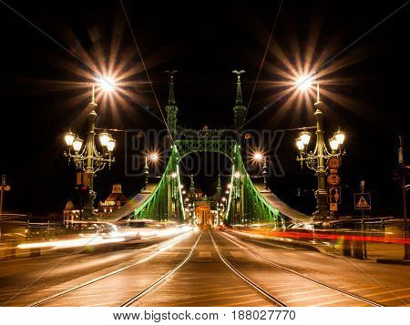 Front view of illuminated Liberty bridge in Budapest, Hungary. Night shot long exposure with car lights.