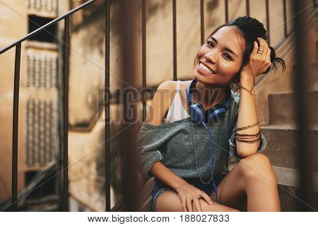 Beautiful Asian woman with messy hair bun posing for photography while sitting on shabby stairs, view through steel stair railing