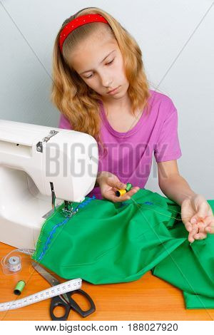 Girl teenager choose a suitable color thread for sewing fabrics