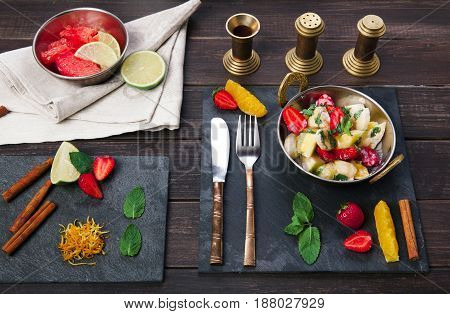 Vegetarian restaurant food. Indian salad with fruits served in copper bowl on wooden table, top view