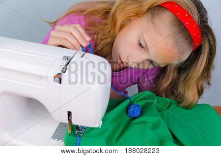 Teen girl frightened by her mistake when sewing on a sewing machine