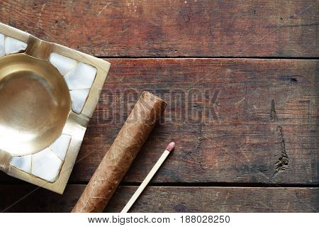 One Cuban cigar near ashtray and matchstick on old wooden background