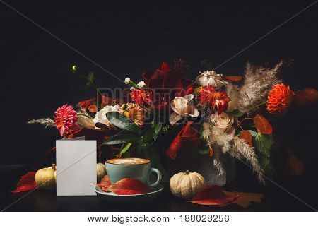 Cappuccino and beautiful flowers composition. Flower shop composition. Coffee cup with foam, apple, fresh and dried flowers bouquet on black wood background. Florist art and floral design concept