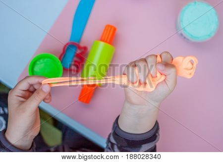 child hands keeping bright orange piece of plasticine above playing table