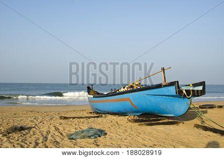 Fishing wooden blue boat on sea coast beach in Karnataka India