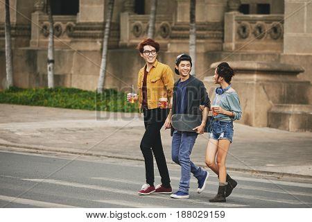 Full length portrait of stylish Asian friends chatting animatedly with each other while crossing street