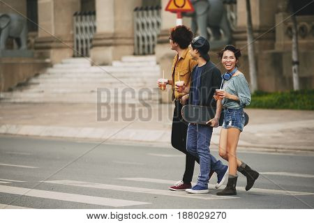Joyful young friends with plastic cups of iced tea in hands crossing street in city center, full length portrait