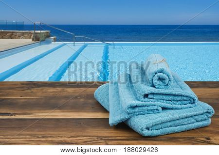 Towels on wooden over blurred swimming pool and sea background
