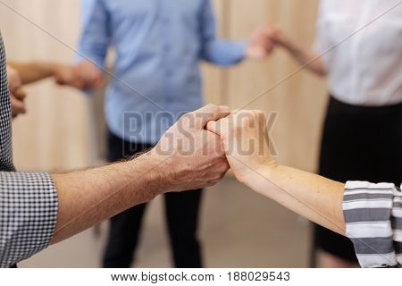 Unity and support. Close up of hands being held together while showing unity and support