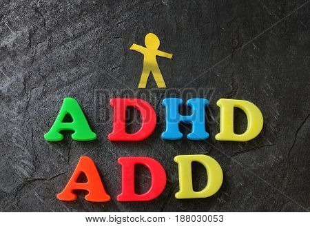 ADD (Attention Deficit Disorder) and ADHD spelled out in play letters with paper child cutout