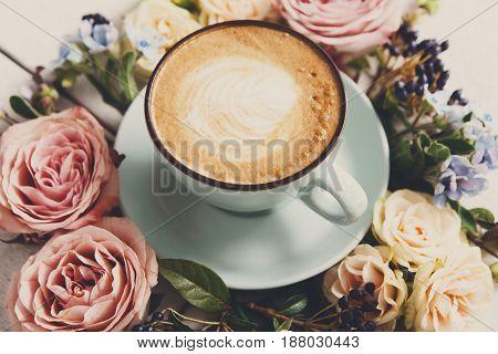 Cappuccino and flowers composition closeup. Blue coffee cup with creamy foam, fresh and dried flowers circle at white wood background. Hot drinks, seasonal offer concept