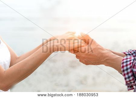 Young couple in love Attractive man and woman enjoying romantic evening on the beach Holding hands watching the sunset