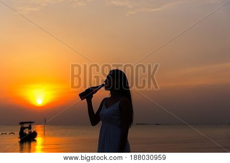 Silhouette woman raised hands holding beer bottle on the sunset sky