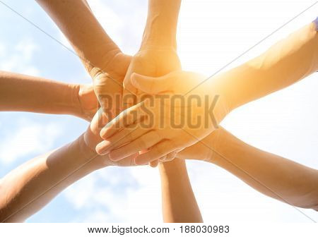 Hands of people team close up on blue sky background