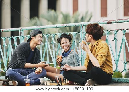 Young Asian friend enjoying each others company while eating delicious sandwiches and playing chess, full length portrait