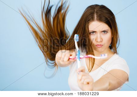 Woman Holding Two Toothbrushes Crossed