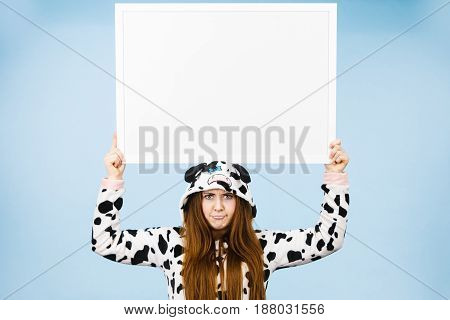 Teenage girl in funny nightclothes pajamas cartoon style with blank empty banner board. Advertisement copyspace.