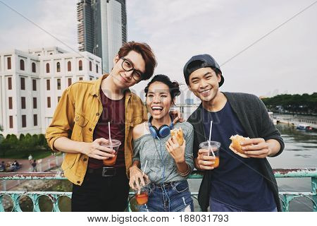 Carefree young friends looking at camera with wide smiles while leaning against bridge railing, waist-up portrait