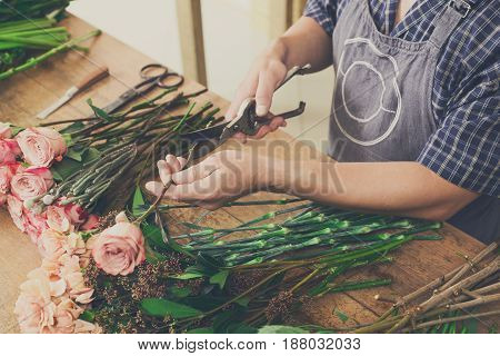 Small business, flowers delivery. Male florist crop, cuts rose for bouquet. Man assistant or owner in floral design studio, making decorations and arrangements.