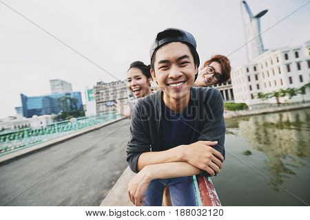 Portrait of handsome young man looking at camera with toothy smile, his friends standing behind him and posing for photography