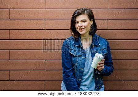 Cheerful Girl With A Cup Of Coffee Near A Brick Wall