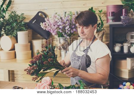 Small business. Male florist making bouquet in flower shop. Man assistant or owner in floral design studio, making decorations and arrangements. Flowers delivery, creating order. Filtered