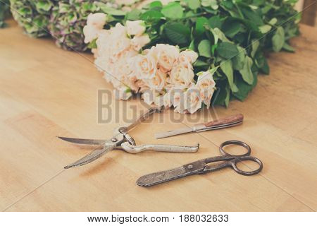 Florist working tools and accesories, cutting fresh roses for bouquet in flower shop. Floral design studio, making decorations and arrangements. Flowers delivery, creating order