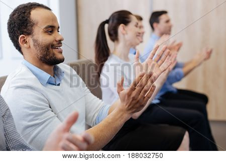It is great. Happy handsome nice man sitting in the first row and applauding while being in a great mood