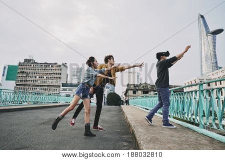Profile view of young man wearing VR glasses wrapped up in playing video game and approaching to edge of bridge, his worried friends trying to stop him