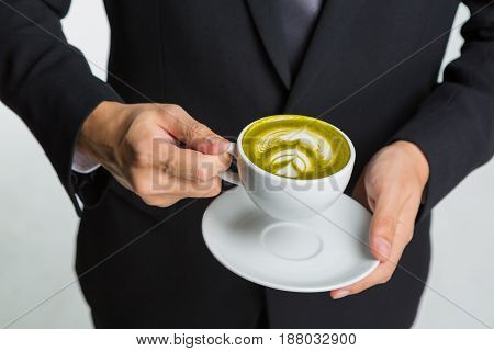 hands of businessman holding a cup of coffee or green tea on white background