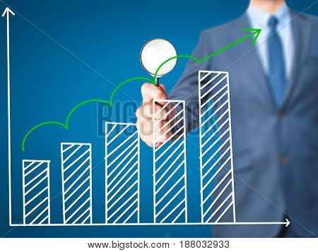 Sales Growth Graph - Business man holding magnifying glass on screen interface. Business technology internet concept. Stock Photo