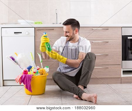 Man With Cleaning Supplies In Kitchen