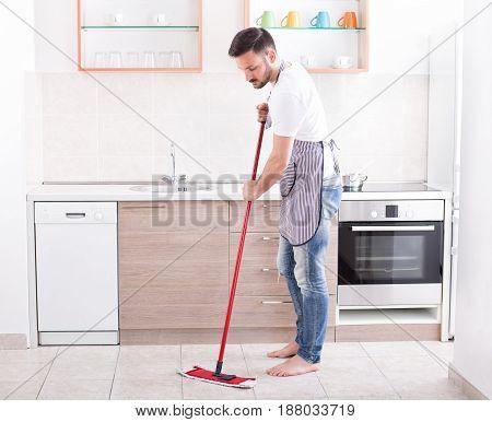 Man Mopping Floor In Kitchen