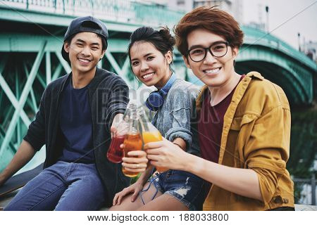 Group portrait of smiling Vietnamese friends looking at camera while toasting with soft drink bottles