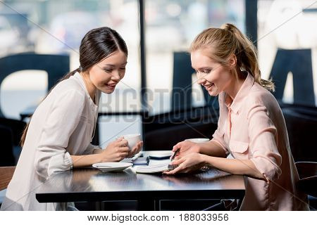Smiling Young Businesswomen Looking At Notebook And Discussing Project At Coffee Break