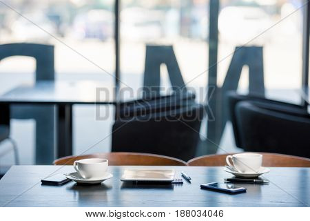 Coffee cups on saucers and digital devices on wooden table in cafe business lunch concept