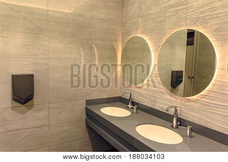 A Bathroom With A Washbasin And Mirrors